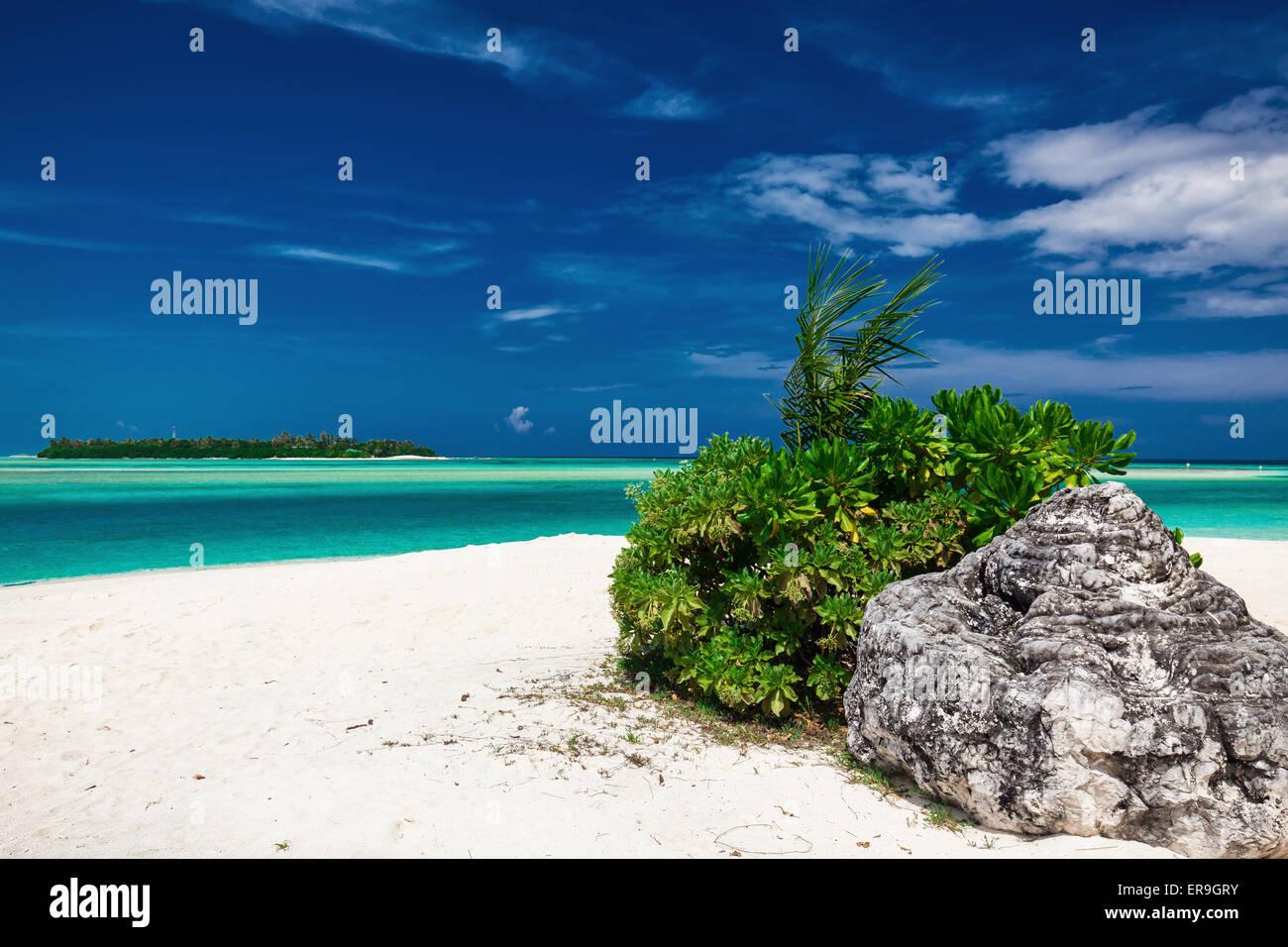 Verträumte kristallklaren Meer mit einem Stein auf den weißen Sandstrand Stockbild