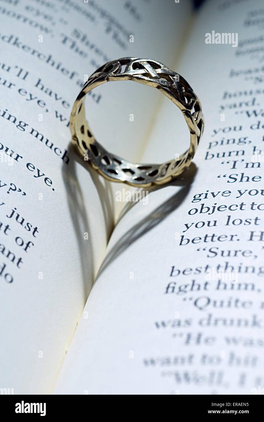 Ring mit herzförmigen Schatten auf ein offenes Buch liegend Stockfoto