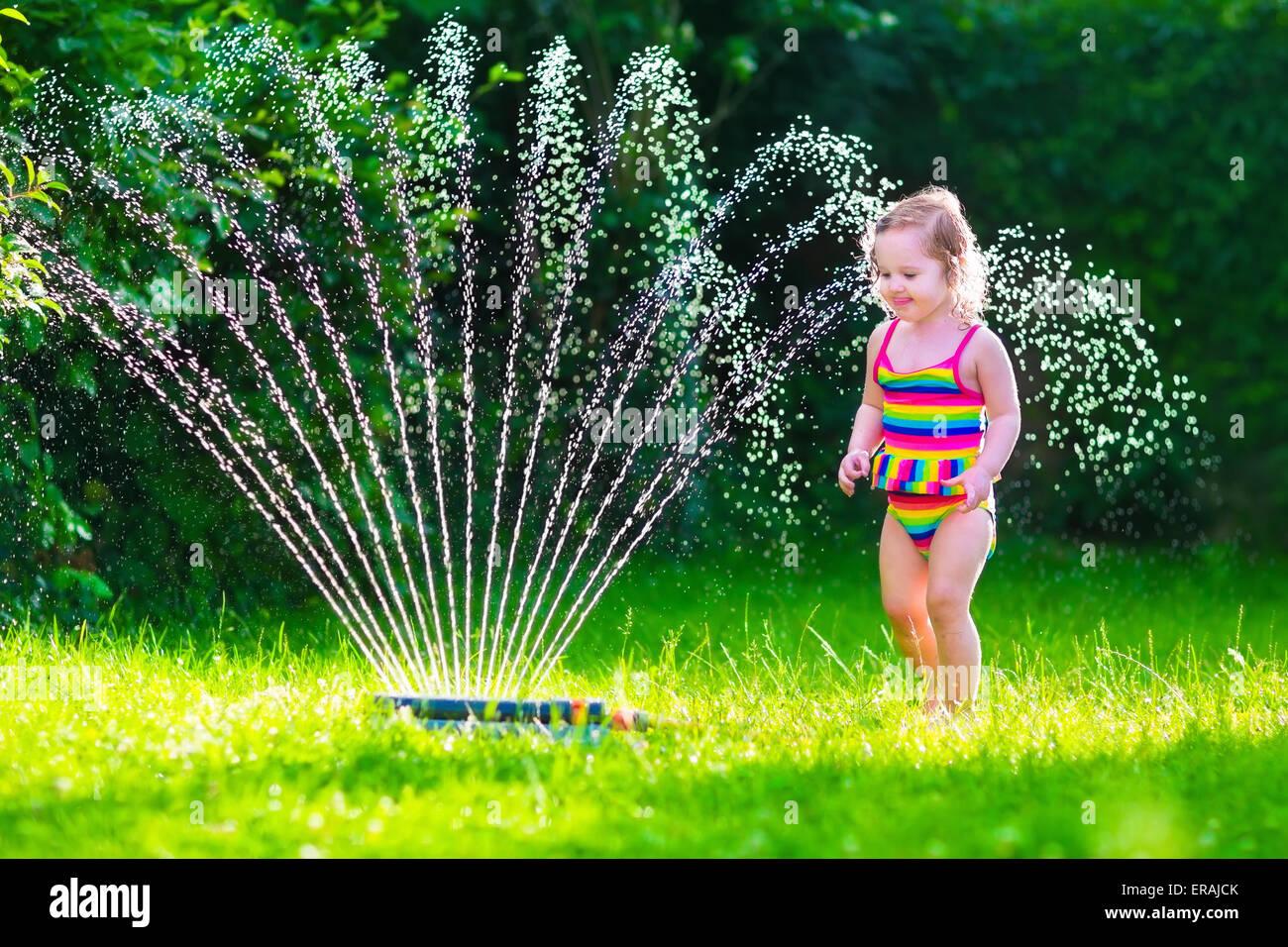 kind spielt mit garten sprinkler kid im badeanzug laufen und springen kinder im garten. Black Bedroom Furniture Sets. Home Design Ideas