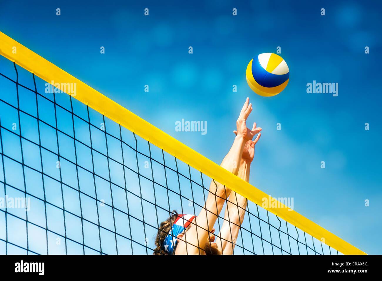 Beachvolley Ball Spieler Sprünge auf dem Netz und versucht, den Ball blockiert Stockbild