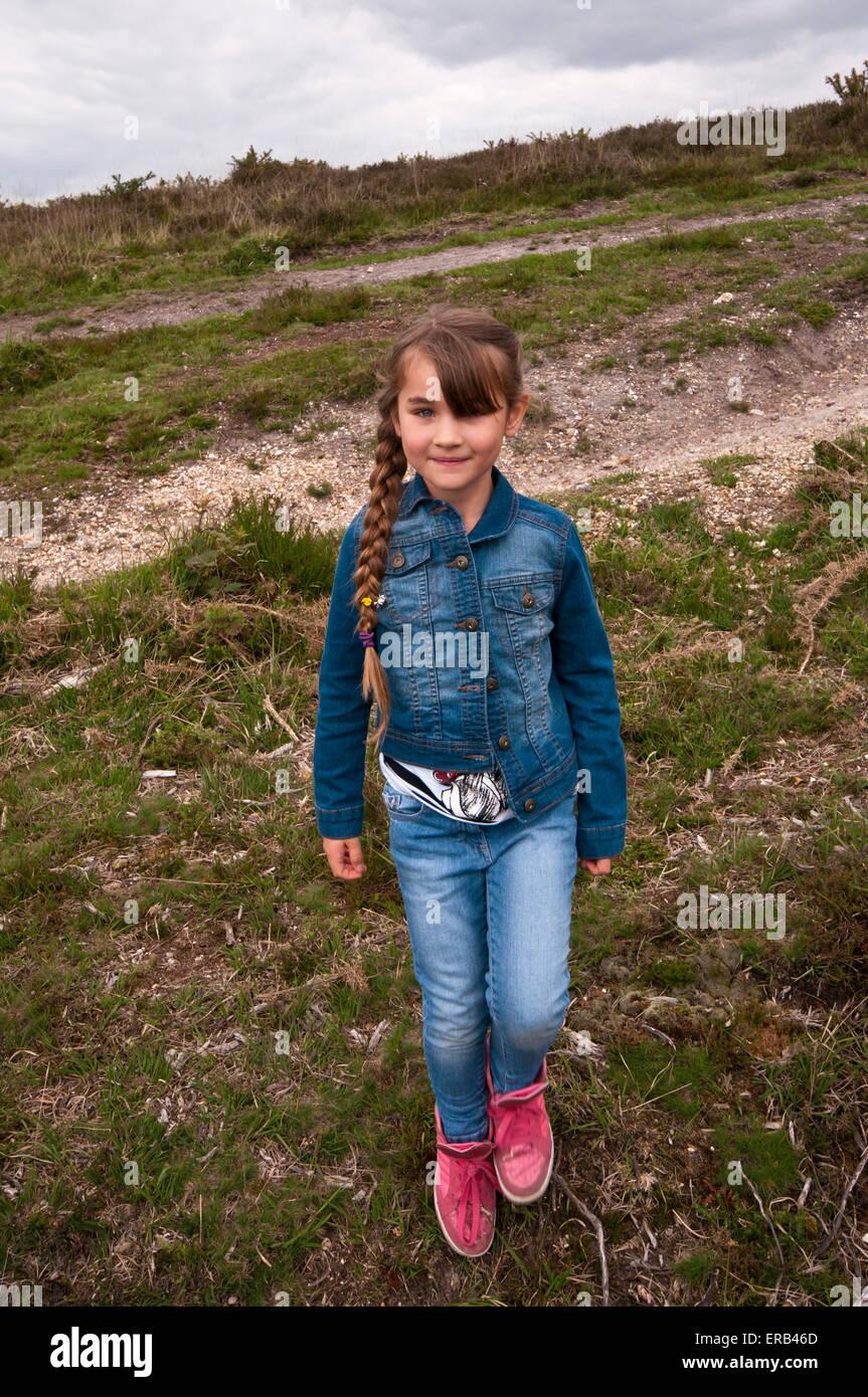 6-jährige Mädchen tragen Jeans Jeans mit langen Haaren In einem Pferdeschwanz im freien Stockbild