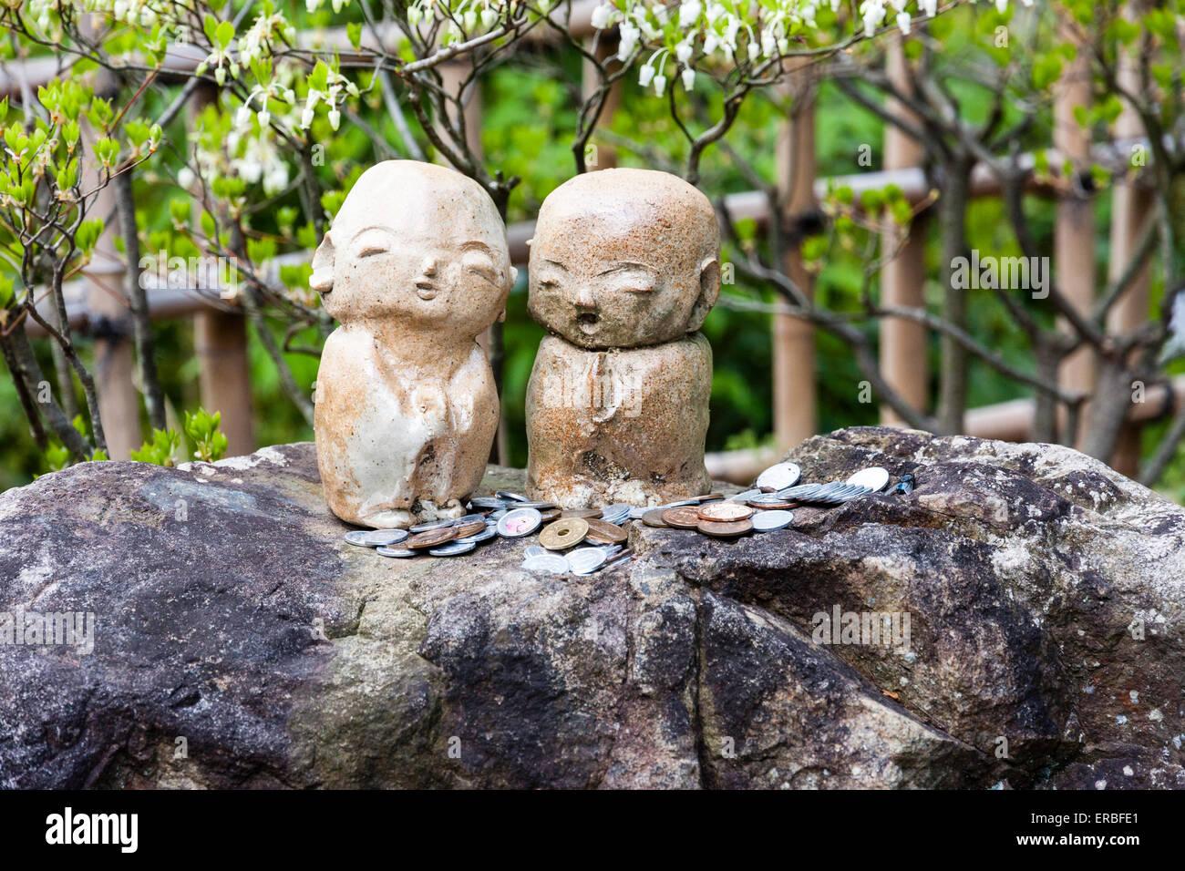 Japan, Kyoto, Chion-in Tempel. Zwei Jizo kleine Statuen, legen Sie als Paar, auf einem Felsen, mit Münzen verstreut Stockbild