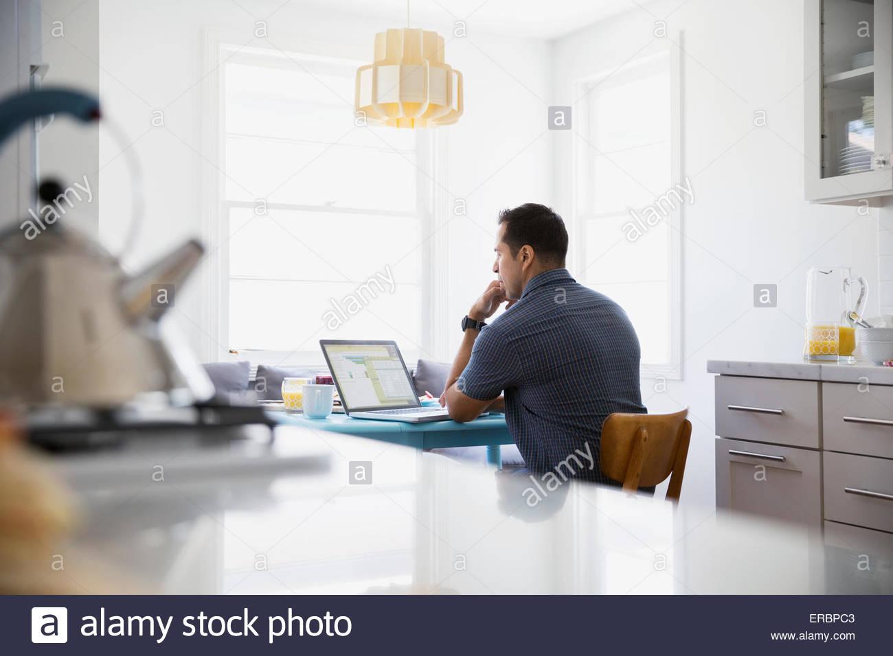 Ernster Brünette Mann mit Laptop am Küchentisch Stockfoto