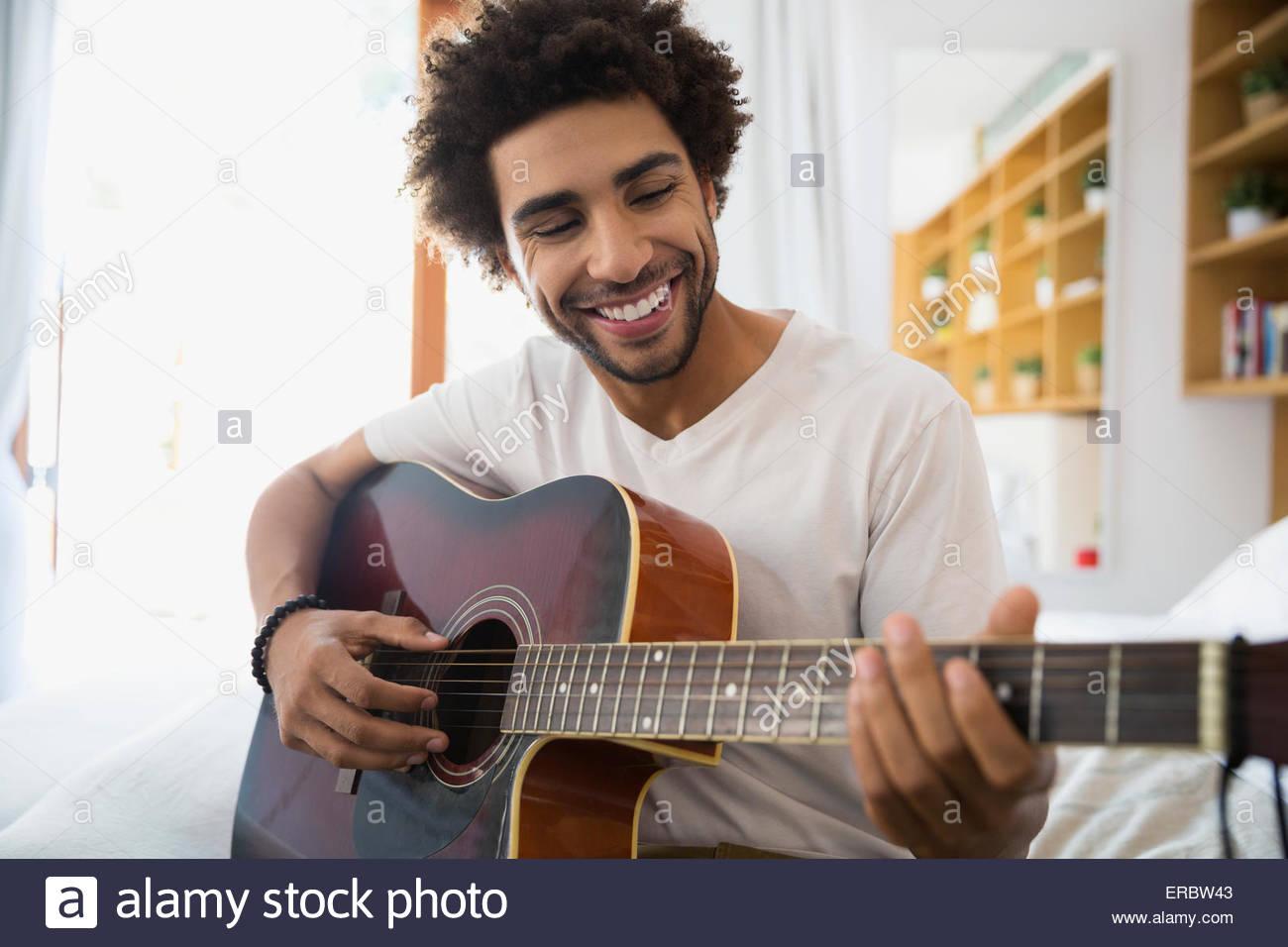 Lächelnder Mann spielt Gitarre im Schlafzimmer Stockbild