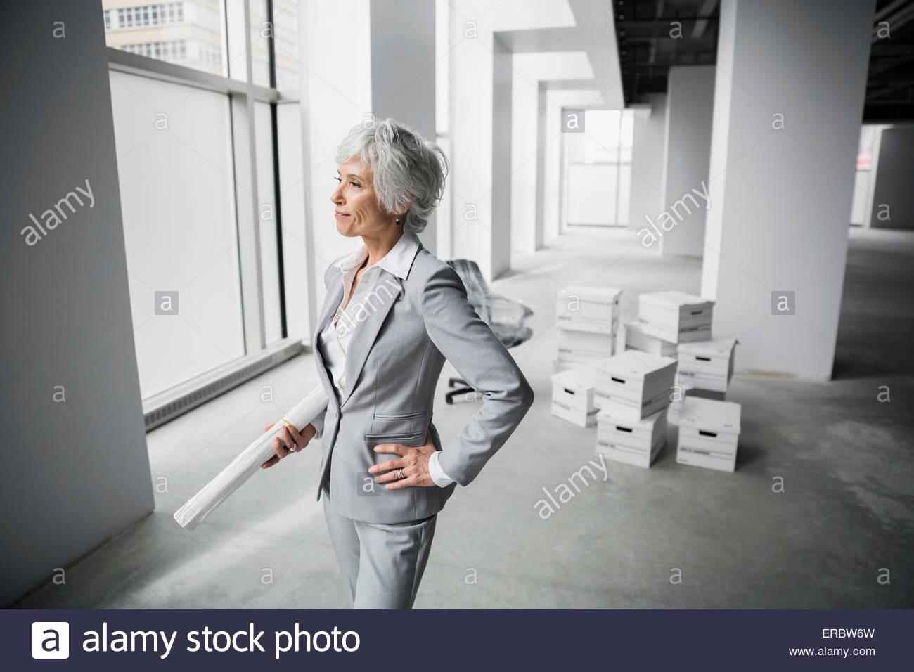 Zuversichtlich Architekt mit Blaupausen in neues Büro Stockbild