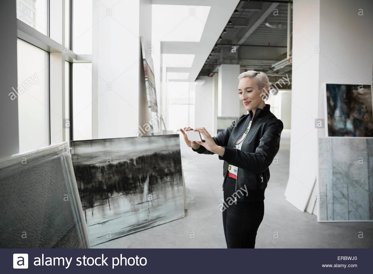 Kunsthändler fotografieren Gemälde mit Kamera-Handy Stockbild