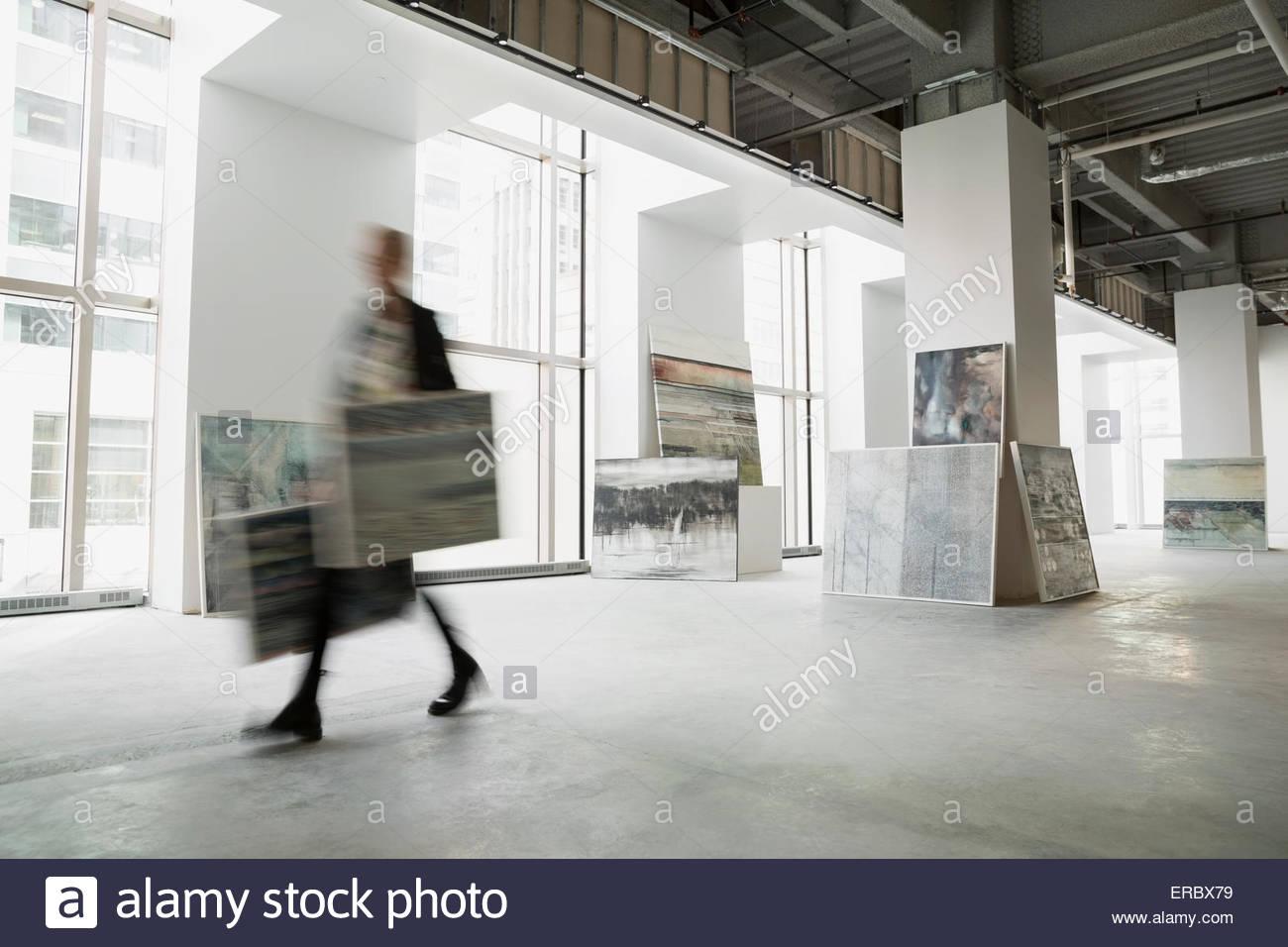 Kunsthändler zu Fuß mit Gemälden in Kunstgalerie Stockbild