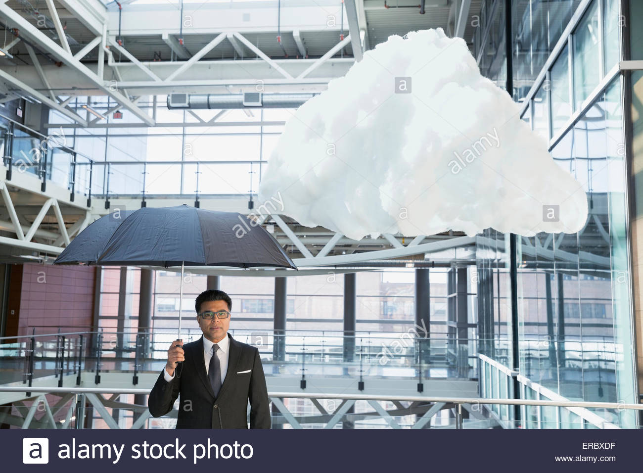 Porträt-Geschäftsmann mit Regenschirm unter Wolke im atrium Stockbild
