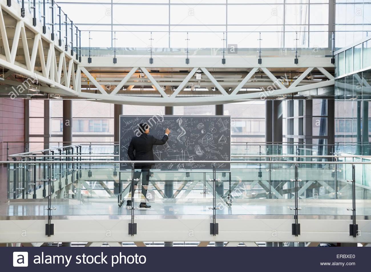 Geschäftsmann an der Tafel mit komplexen Gleichungen im atrium Stockfoto