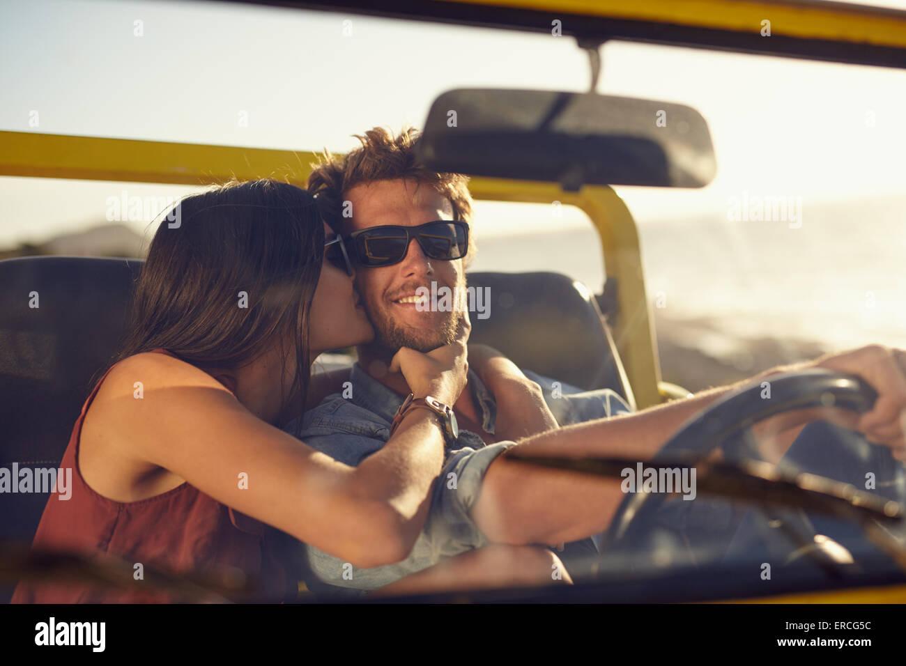 Junges Liebespaar auf Roadtrip. Frau ihres Freundes Wangen küssen. Junger Mann, ein Auto zu fahren. Romantische Stockfoto
