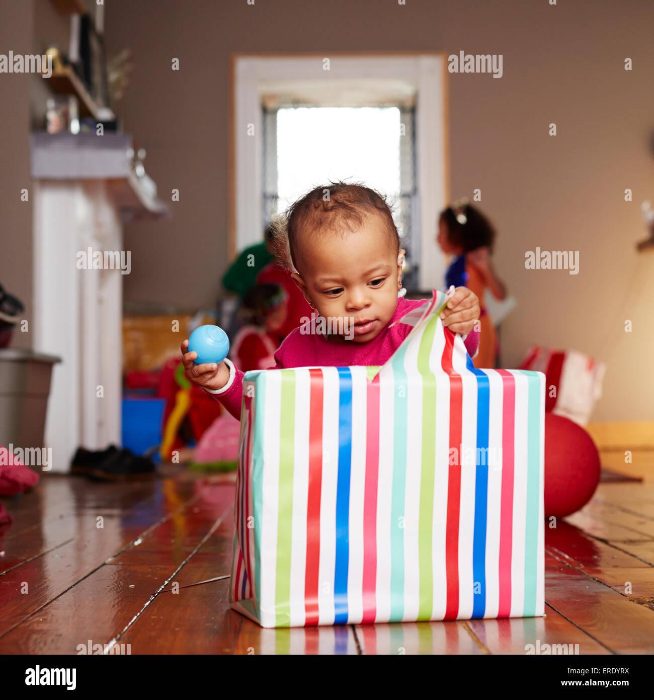 Gemischte Rassen Mädchen Eröffnung Geschenk im Wohnzimmer Stockfoto