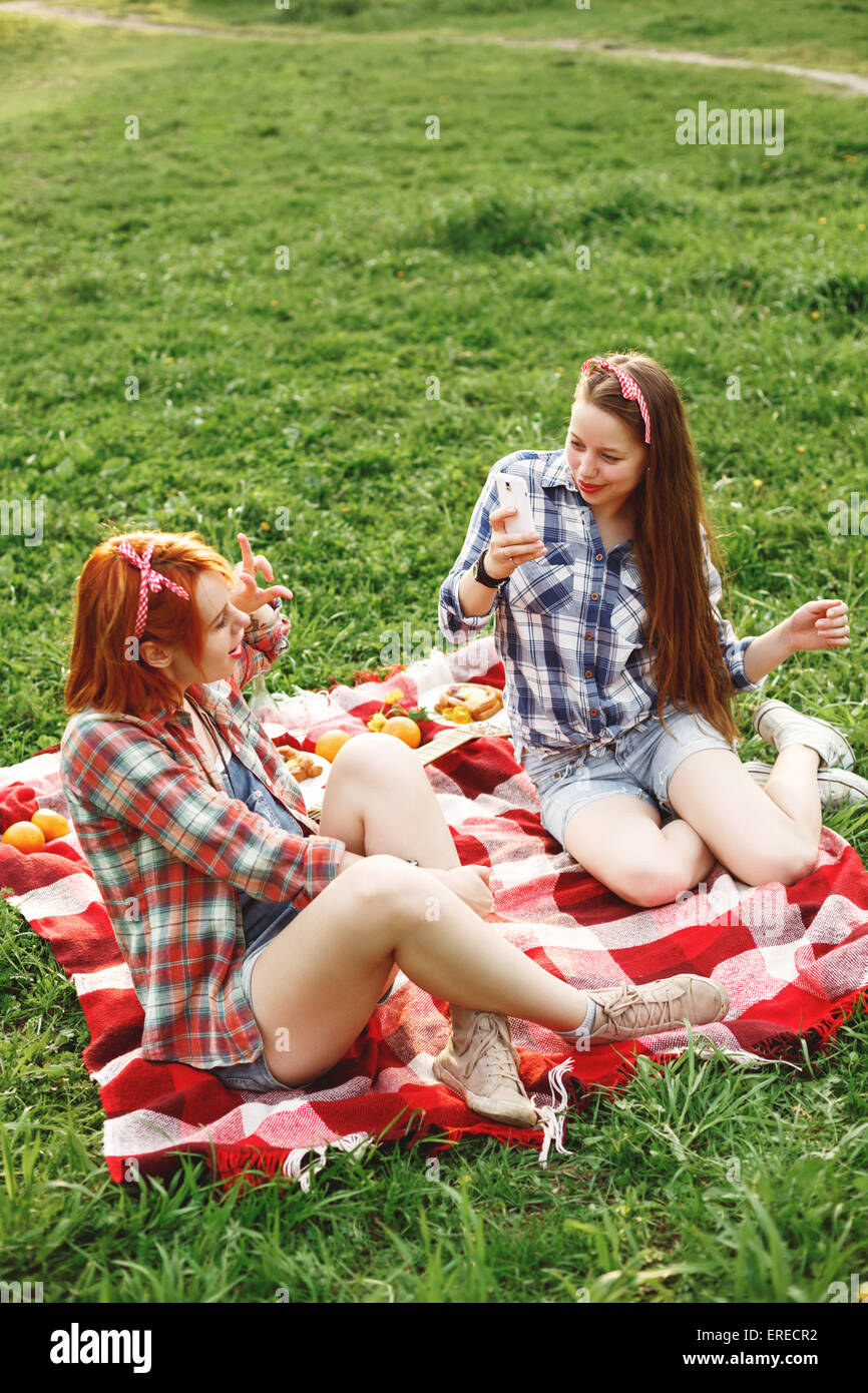 Zwei glückliche Mädchen fotografieren einander auf dem Handy für Instagram. Sommer-Abend-Picknick. Stockbild