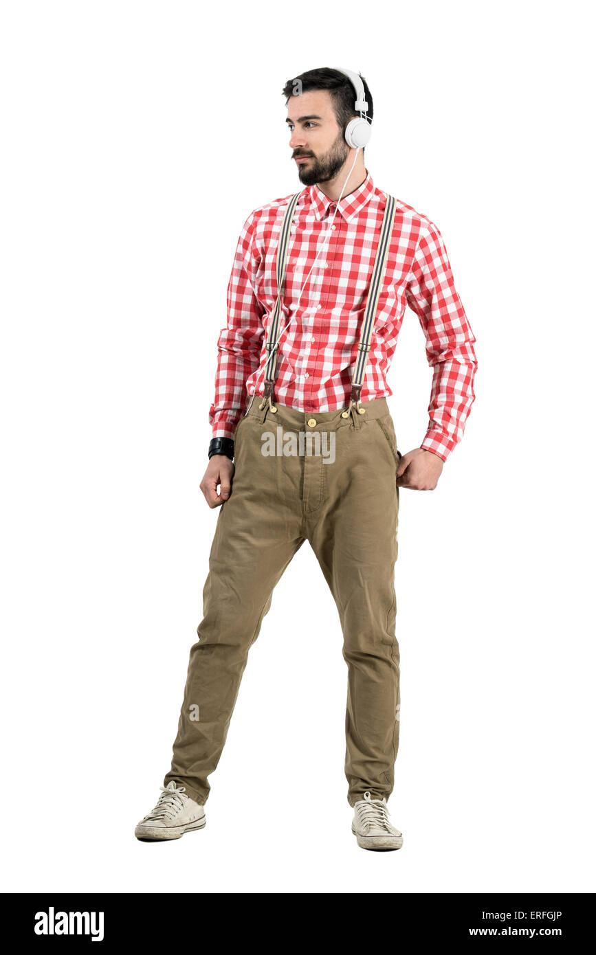 Junge Hipster posiert mit Kopfhörer wegsehen. Ganzkörper-Länge-Porträt isoliert auf weißem Stockbild