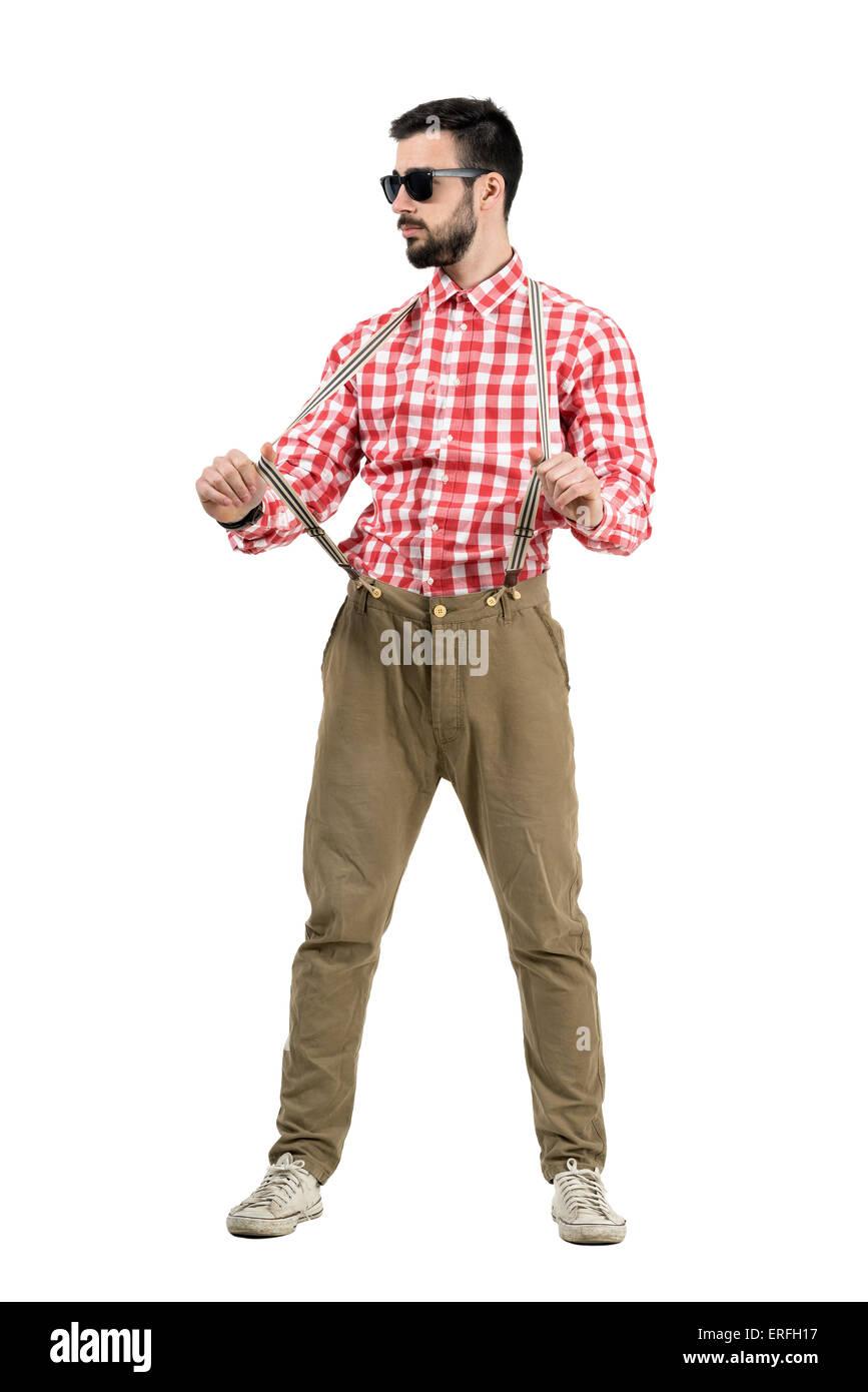 Junge bärtige Hipster ziehen Strapse wegsehen. Ganzkörper-Länge-Porträt isoliert auf weißem Stockbild