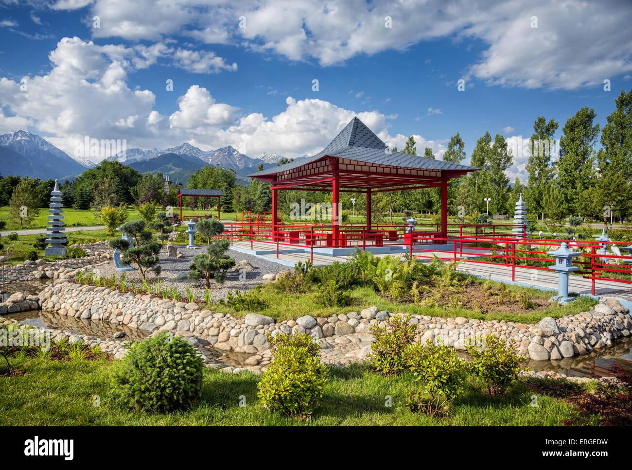 Japanischer Garten mit rote Pagode am Berge und blauer Himmel in Dendra Park des ersten Präsidenten in Almaty, Stockbild