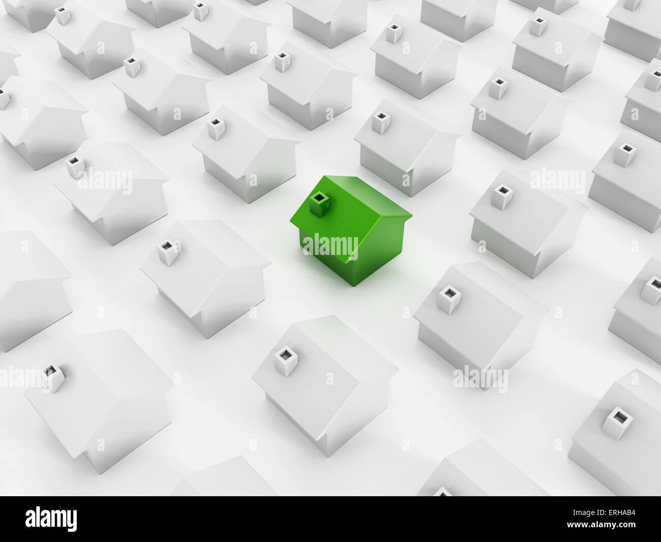 Grüne Haus zeichnet sich unter weißen Häusern. Stockbild