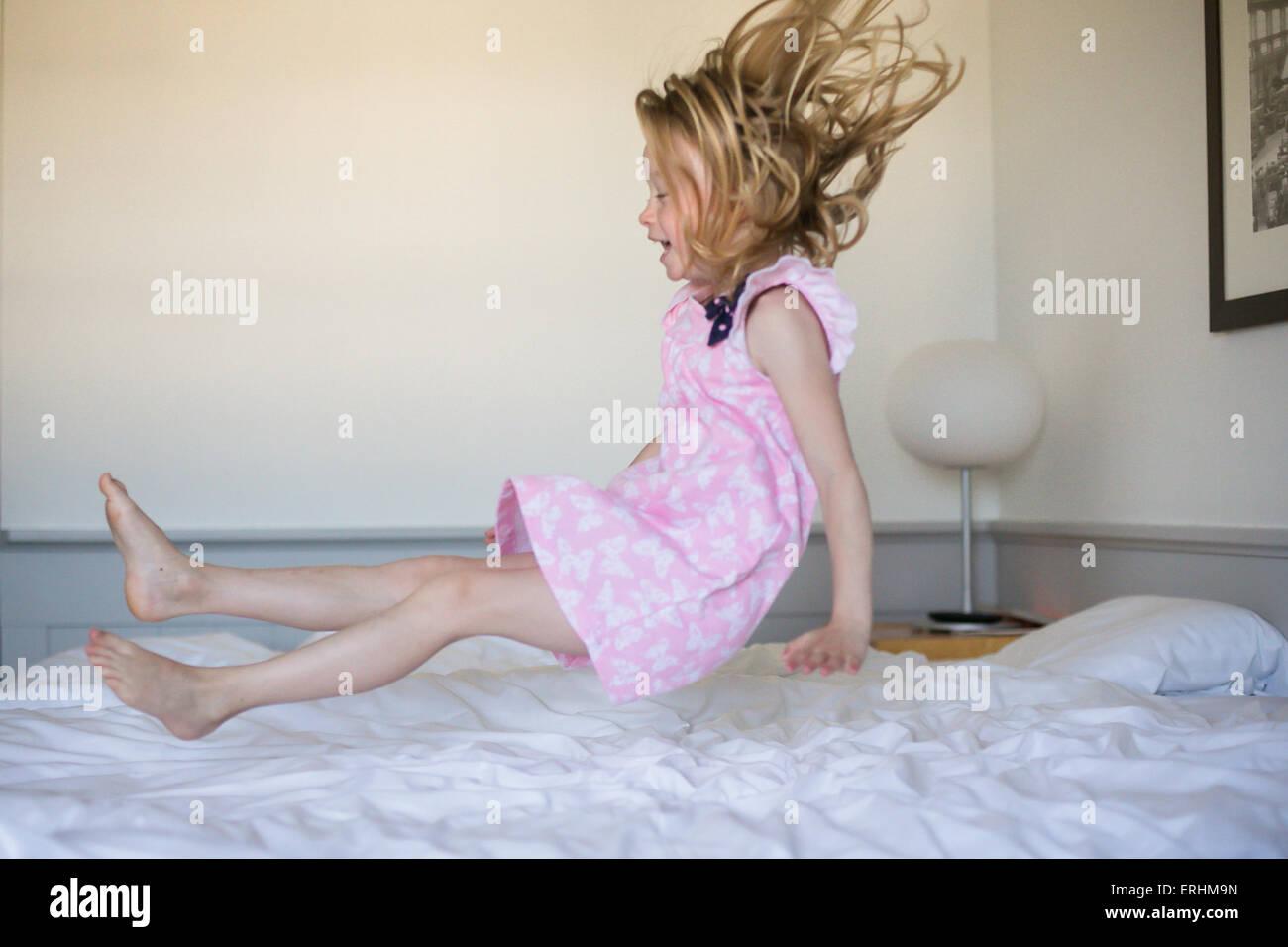 Mädchen auf ihrem Bett hüpfen Stockbild