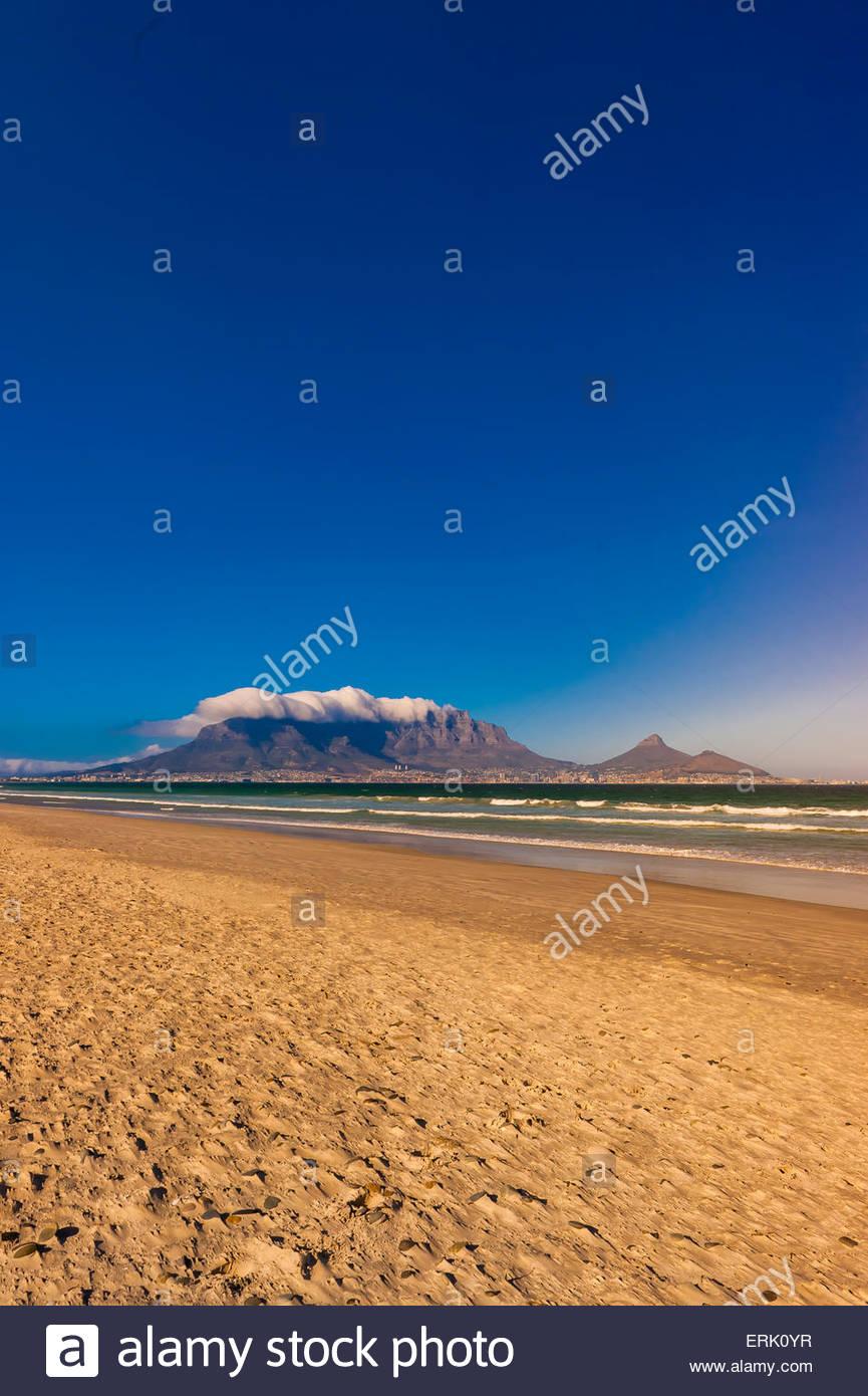 Blick auf Kapstadt und den Tafelberg und Lion es Head Peak vom Strand in Milnerton, Südafrika. Stockbild