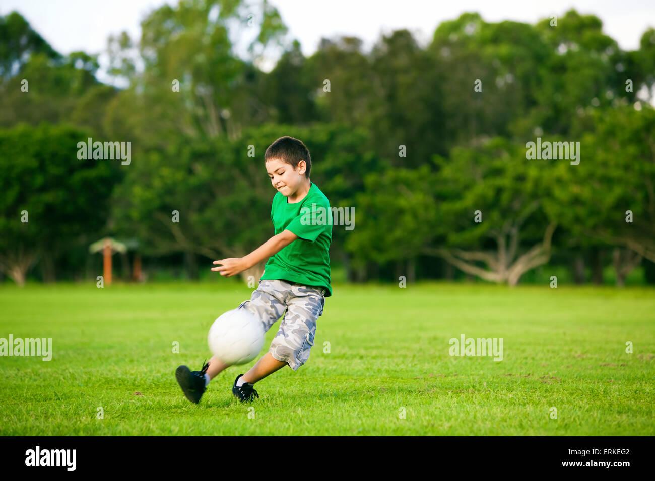 Junge begeistert junge treten Ball auf der Wiese im freien Stockbild