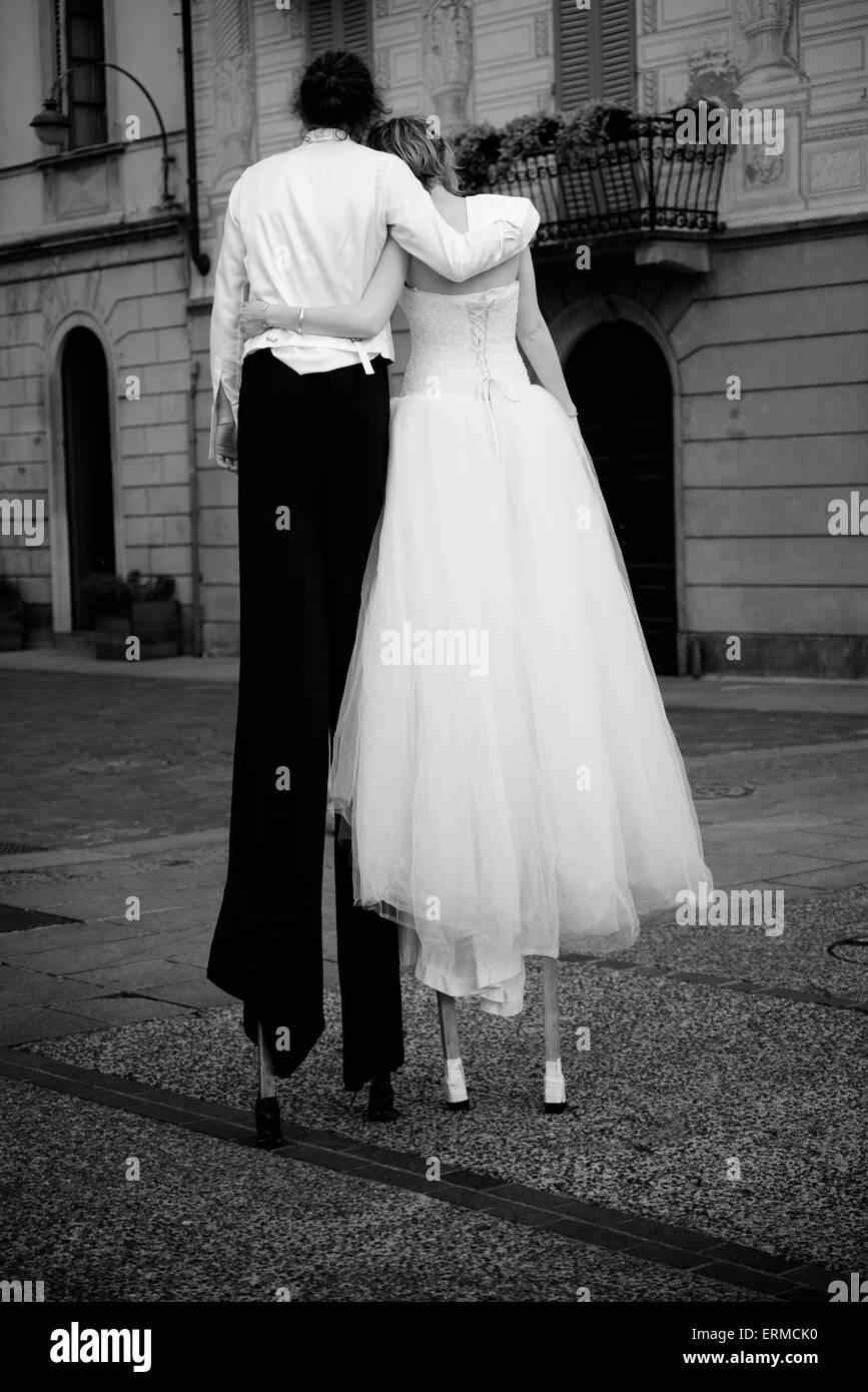 Paar gekleidet wie eine Hochzeit gehen auf Stelzen Stockbild