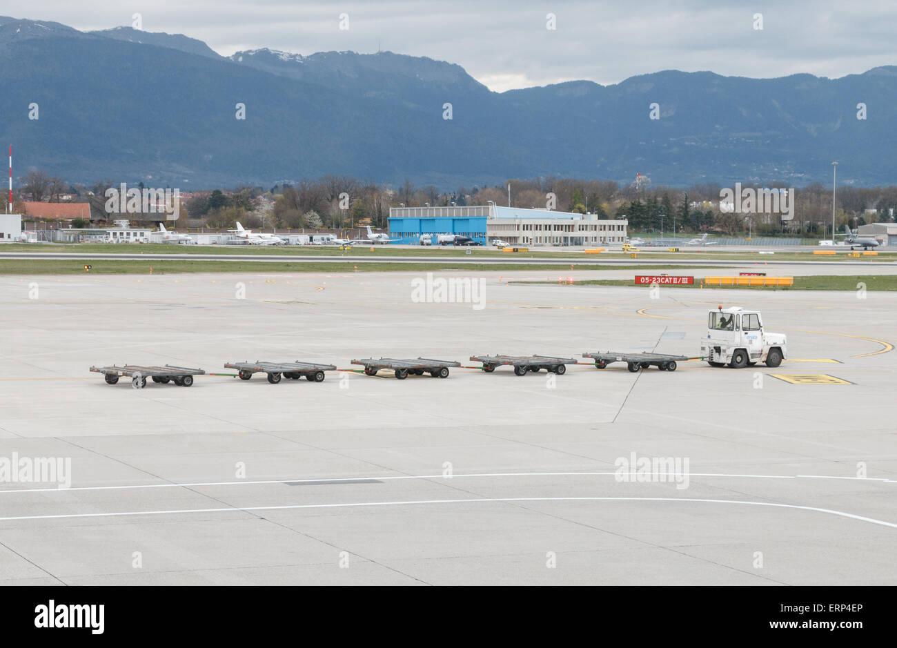 Leere Gepäckwagen am Flughafen Genf über die Rollbahn oder Schürze geschleppt wird.  Konzept, die Stockbild