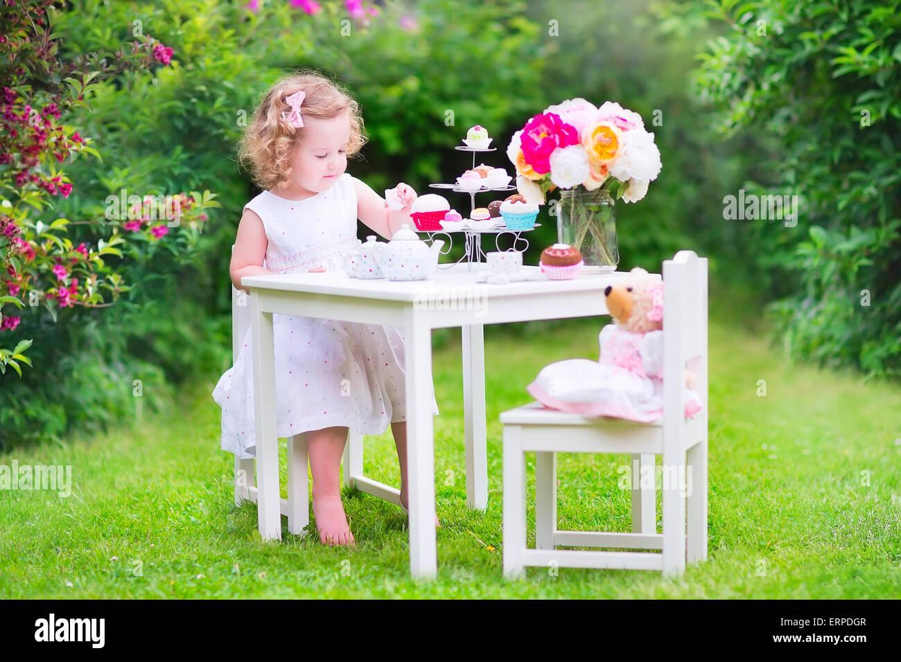Entzückende Kleinkind Mädchen mit dem lockigen Haar trägt ein buntes Kleid an ihrem Geburtstag spielen Teeparty mit einer Puppe Teddybär Stockfoto