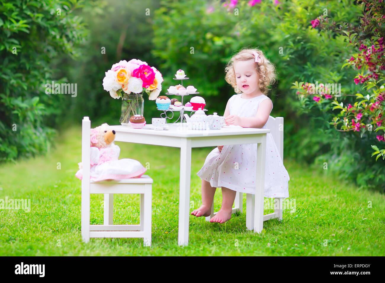 Liebenswert lustige Kleinkind Mädchen mit dem lockigen Haar trägt ein buntes Kleid an ihrem Geburtstag spielen Teeparty mit einer Puppe Teddybär Stockfoto
