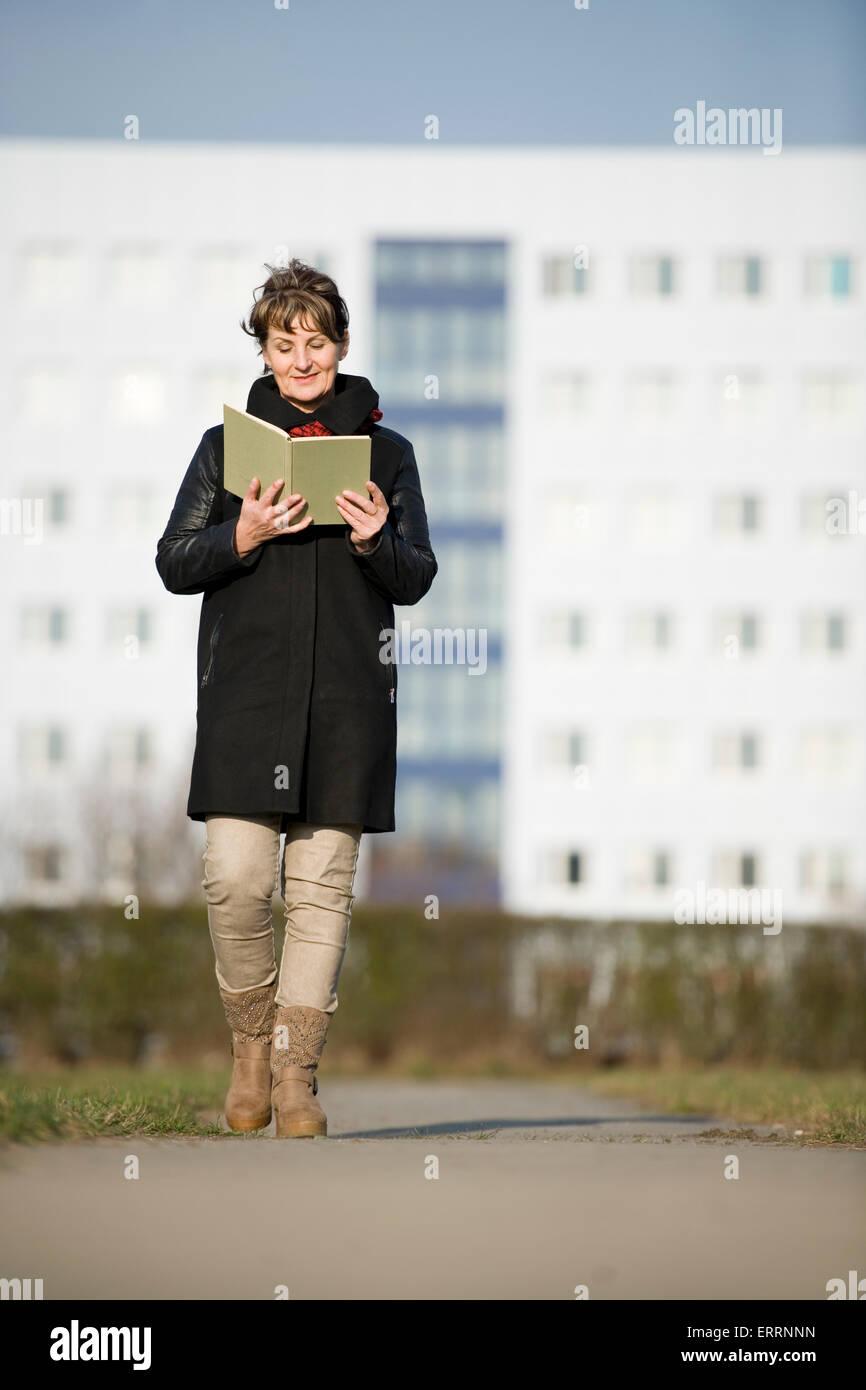 Ganzkörper-Vorderansicht einer reifen Frau in schwarzem Leder Jacke ein Buch lesen auf die Kamera unmittelbar Stockbild