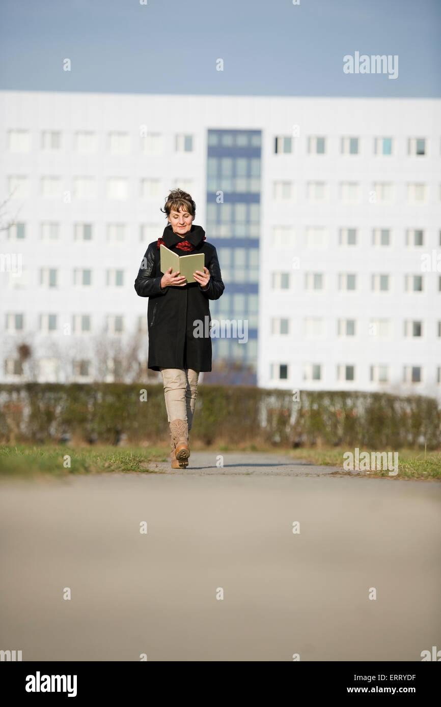 frontale Ganzkörper-Anzeigen einer reifen Frau in schwarzer Lederjacke ein Buch lesen auf die Kamera sofort Stockbild
