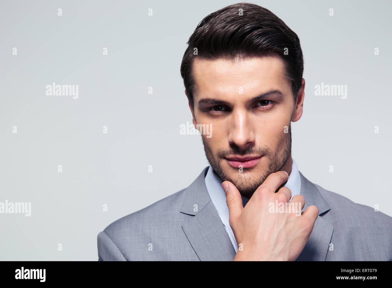 Porträt eines durchdachten Geschäftsmann berühren sein Kinn über grauen Hintergrund Stockfoto