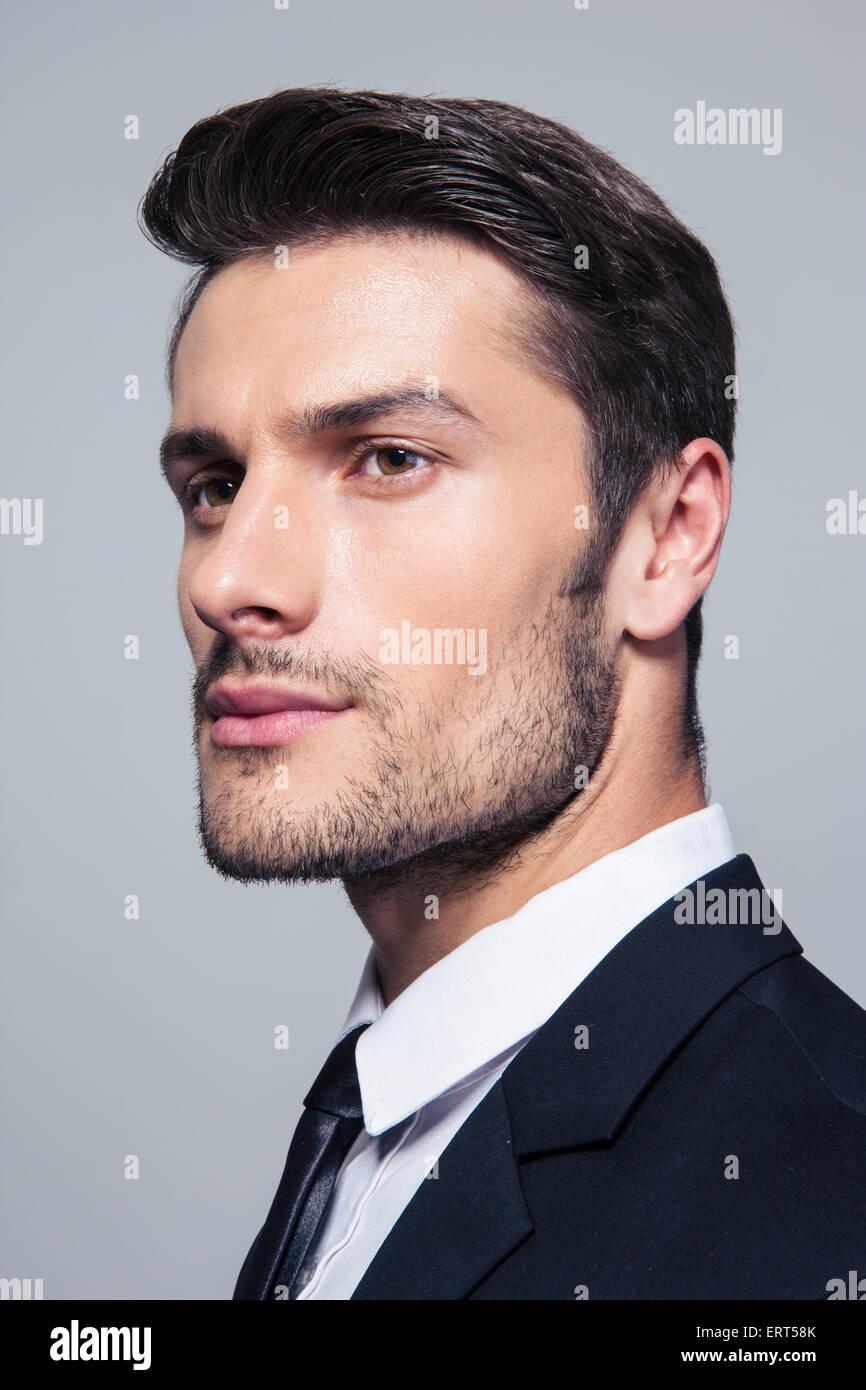 Closeup Portrait eines nachdenklich Geschäftsmannes auf grauem Hintergrund Stockbild