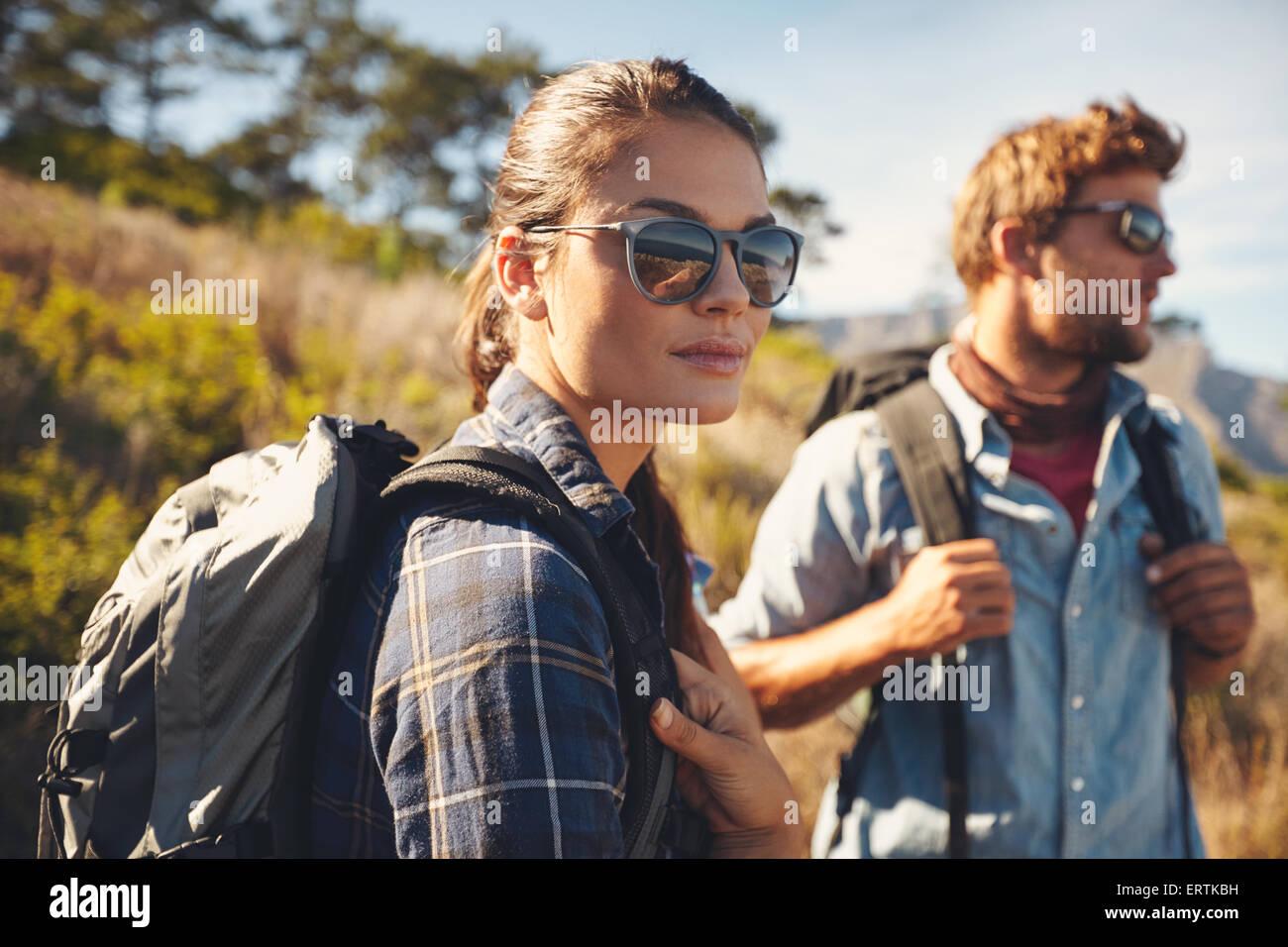 Hübsche junge Frau auf einer Wanderung mit Mann im Hintergrund. Kaukasische paar Wanderung in Landschaft Stockbild