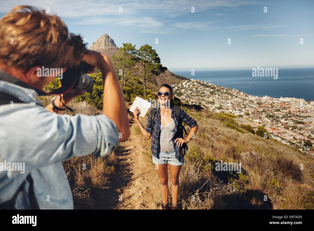 Junger Mann die Fotos von hübschen Freundin zeigt eine Karte in Landschaft beim Wandern in den Sommerferien. Stockbild