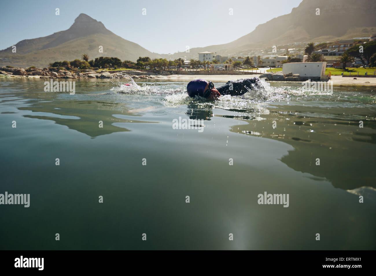Männlicher Athlet im Freiwasser schwimmen. Sportler üben für den Triathlon-Wettbewerb. Stockfoto