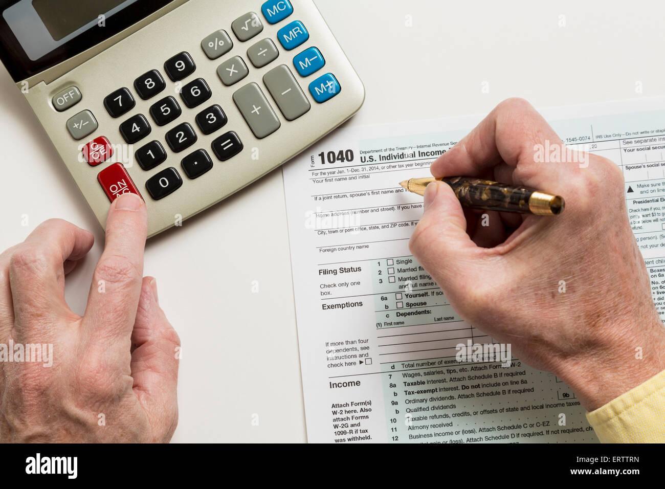 Mann ausfüllen Steuerformular USA Rückkehr 1040 mit Rechner - steuern-Konzept Stockbild