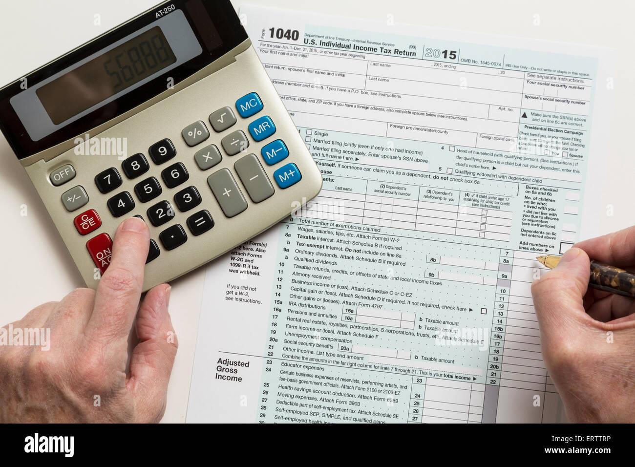 Mann ausfüllen Steuerformular USA 1040 für das Jahr 2015 mit Taschenrechner Stockbild