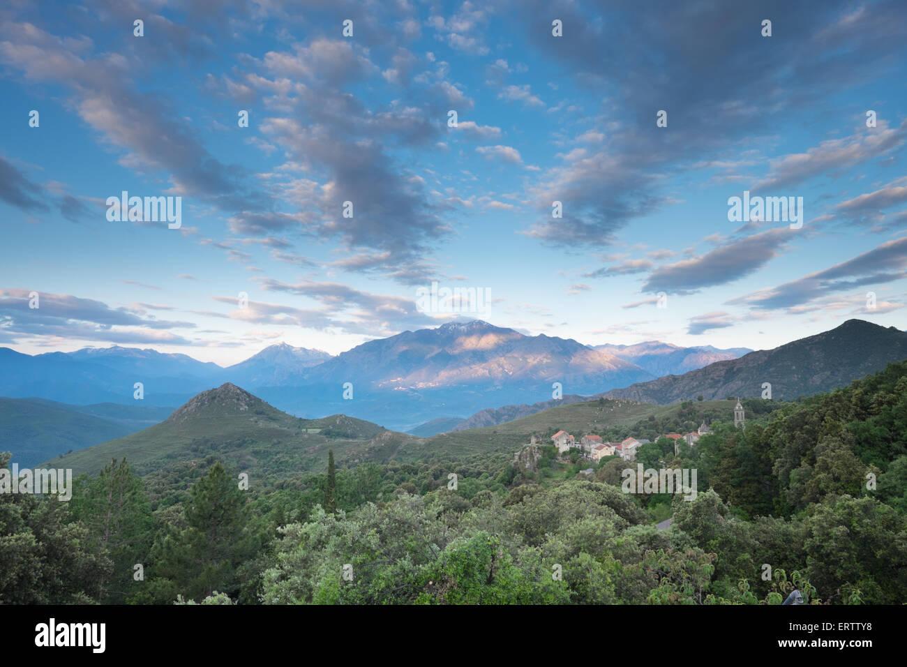 Die aufgehende Sonne wirft seitliche Streifen von Licht auf den Bergen von zentralen Korsika.  Die Wolken erstellen Stockbild