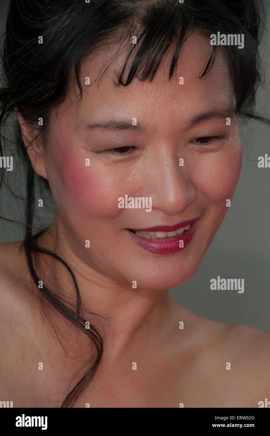 Reife Asiatin mit schönen Teint, auf der Suche nach unten und Weg von der Kamera Stockbild