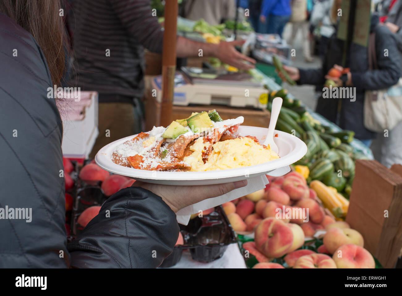 Person mit Frühstücksteller mit Rührei mit Käse und Avocado am Ferry Building Wochenmarkt, San Stockbild