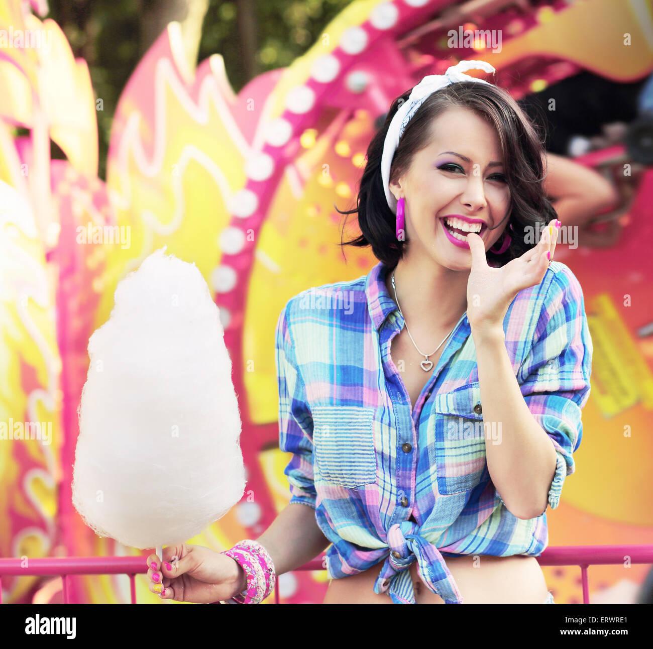 Toothy Lächeln. Junge Frau mit Zuckerwatte im Vergnügungspark Stockbild