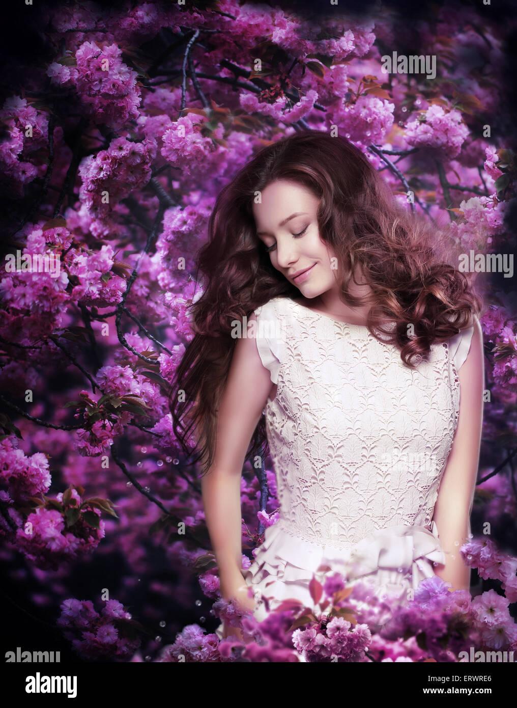 Pure Schönheit. Verträumte junge Frau unter Blütenbäumen Stockbild