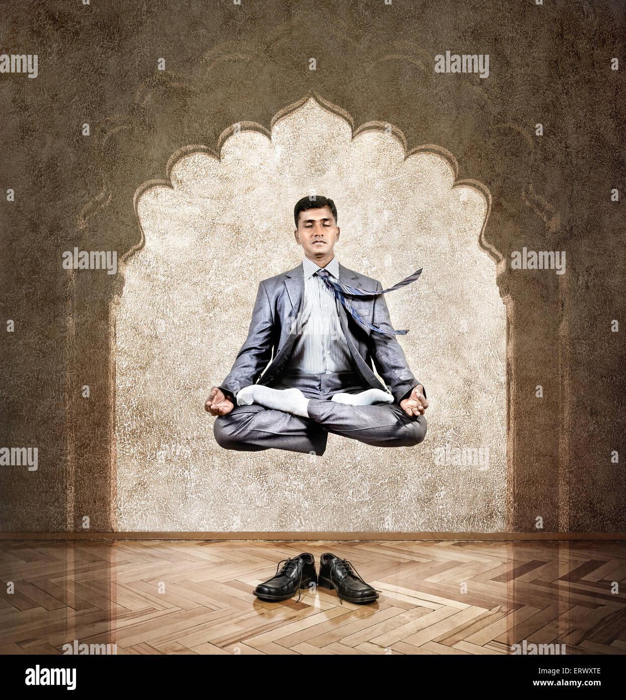 Indischer Geschäftsmann tun Meditation in der Luft in Lotus Pose im Büro mit Bogen an der Wand Stockbild