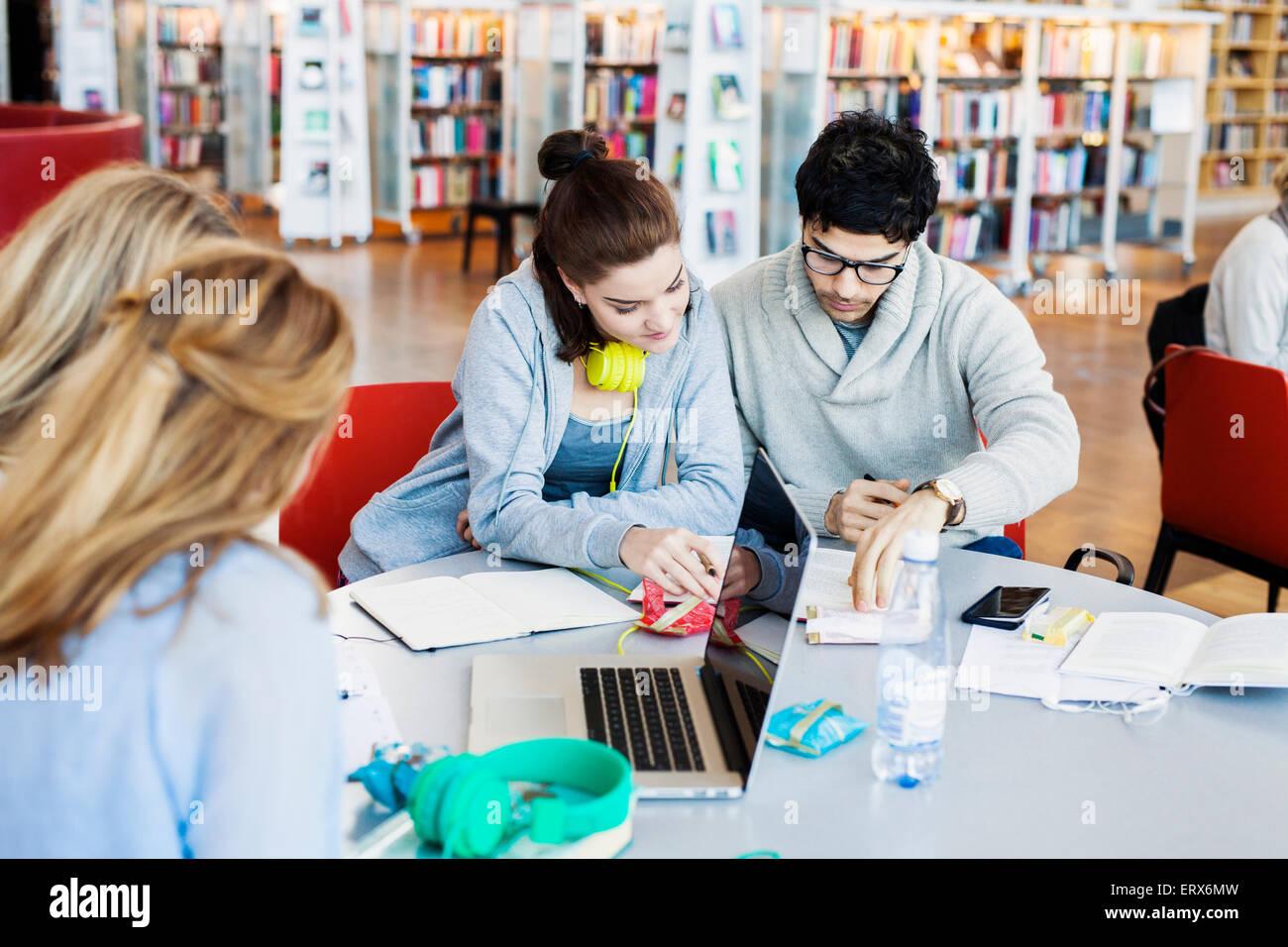 Multiethnische Freunde diskutieren Hinweise am Tisch in Bibliothek Stockbild
