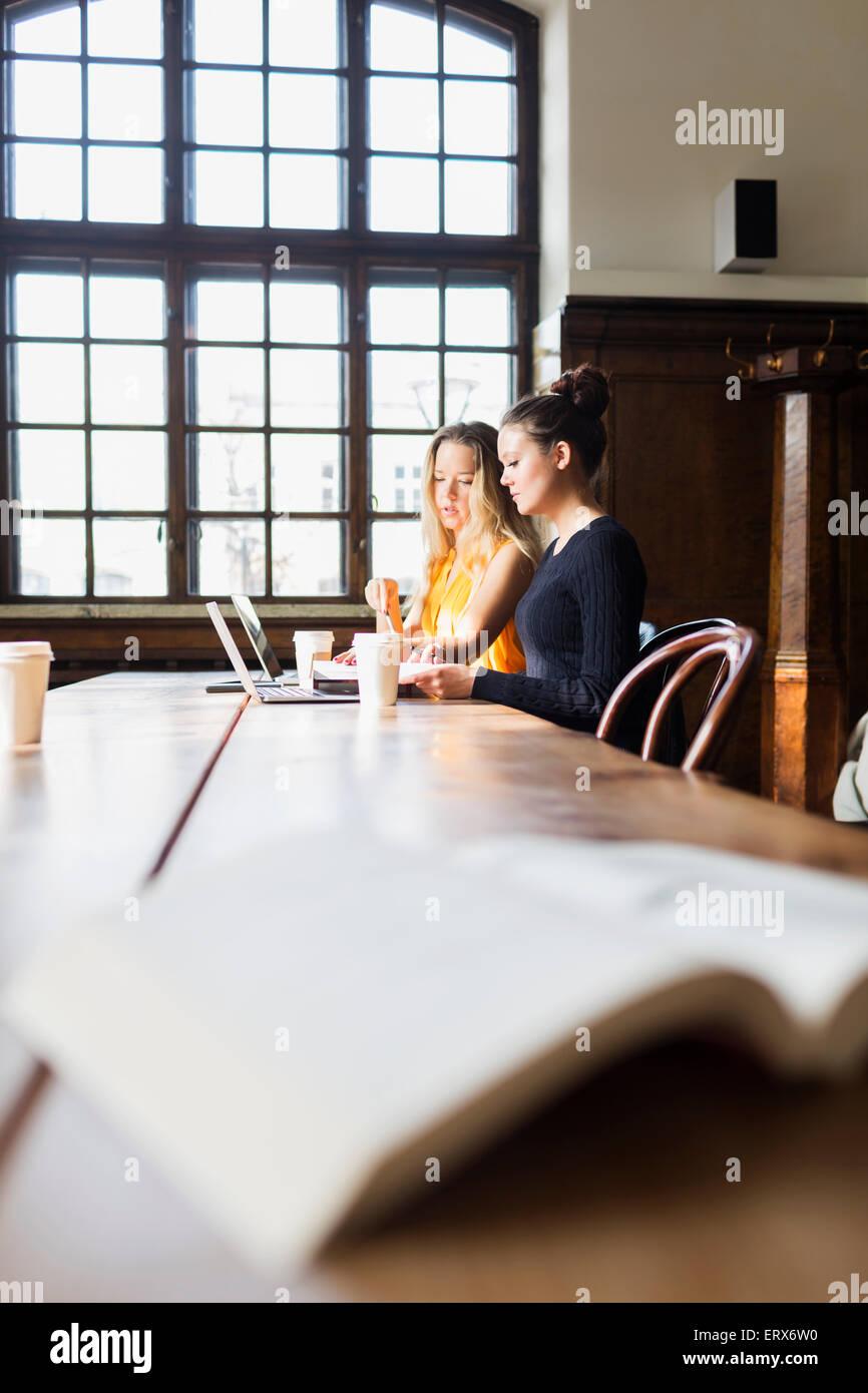 Junge Freunde, die mit Laptops am Tisch im café Stockfoto