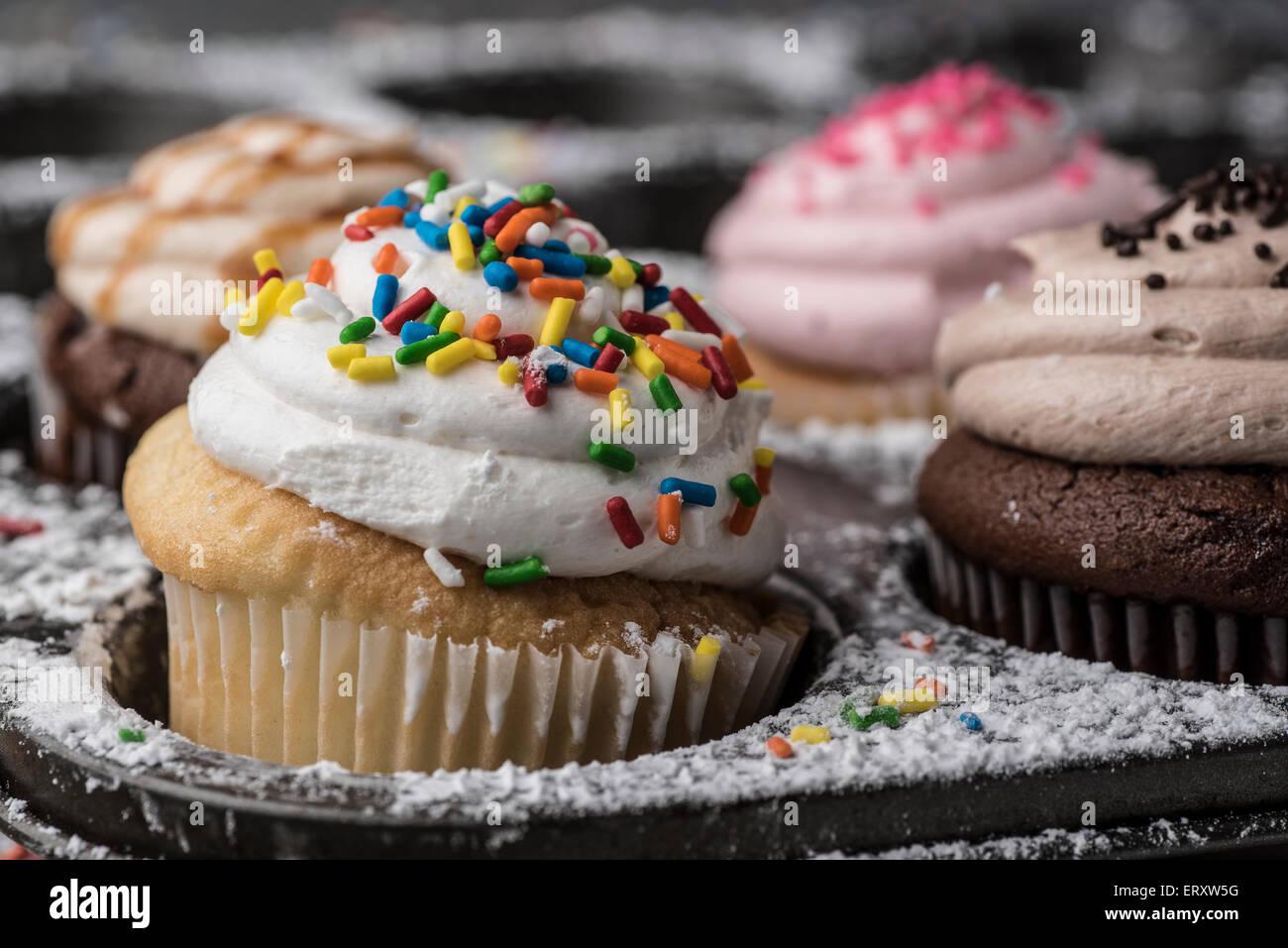 Eine bunte Cupcake umgeben von Zucker und Streuseln Stockbild