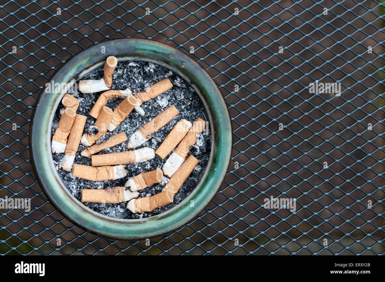Aschenbecher voller Zigarettenstummel auf einem Draht Gitter Tisch ...
