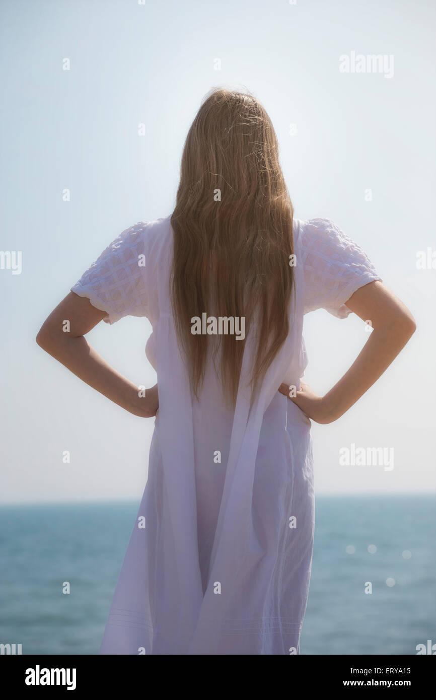 ein Mädchen in einem weißen Kleid von hinten Stockbild