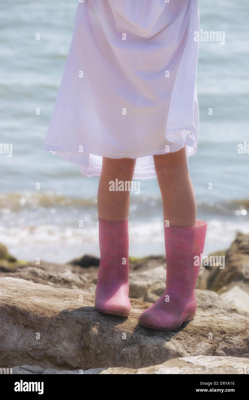 Beine eines Mädchens mit Gummistiefeln auf Felsen am Meer Stockbild