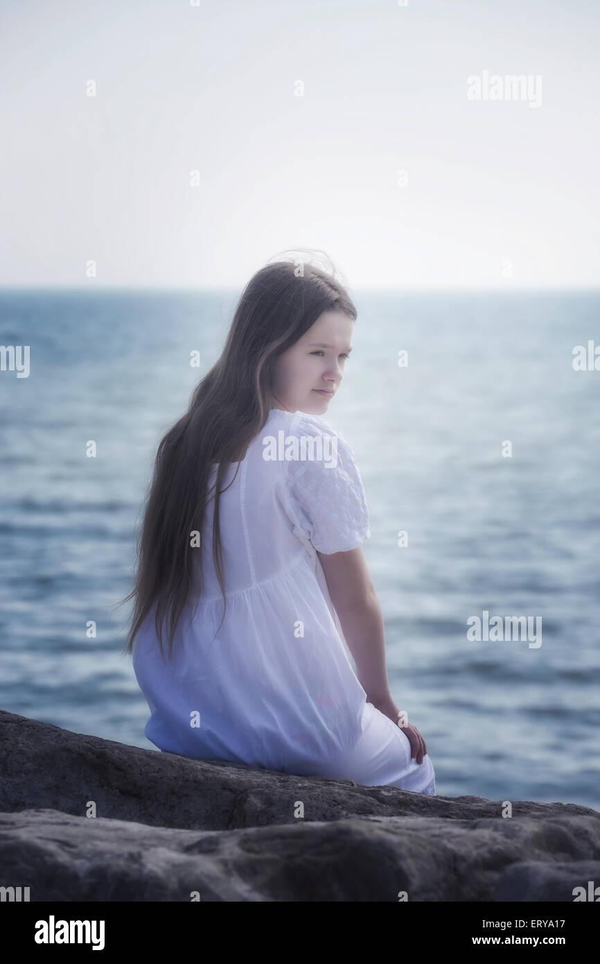 ein Mädchen in einem weißen Kleid sitzt auf den Felsen am Meer Stockbild