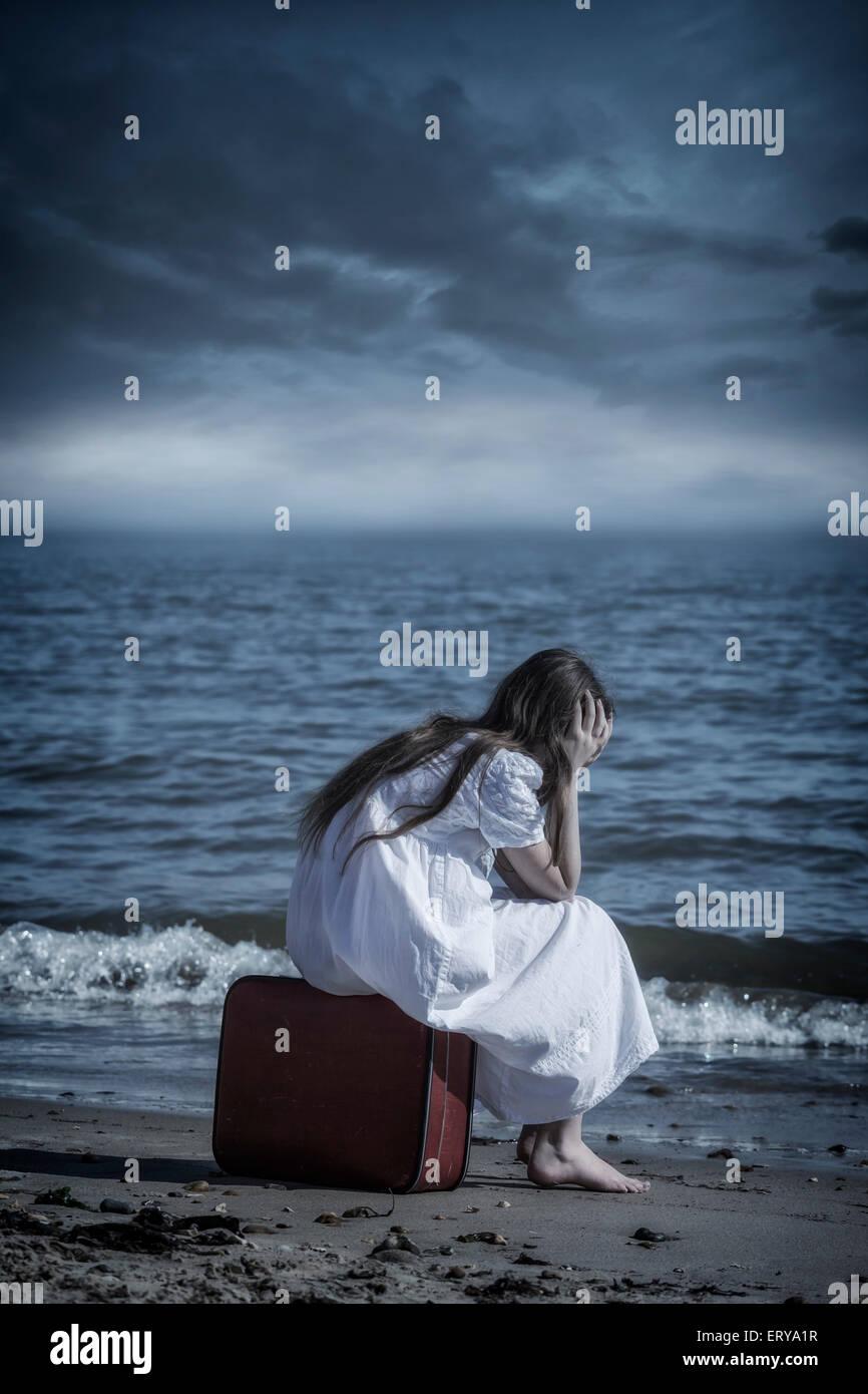 eine Mädchen sitzt auf einem roten Koffer am Meer Stockbild